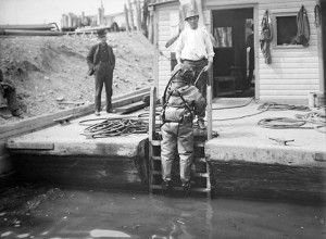 A man in a diving suit, about to descend, ca. 1910.jpg