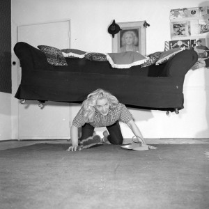 Ken Harding. Glamorous strongwoman Joan Rhodes exercises her strength whilst tackling housework in her flat in Hampstead, north London, March 1958..jpg